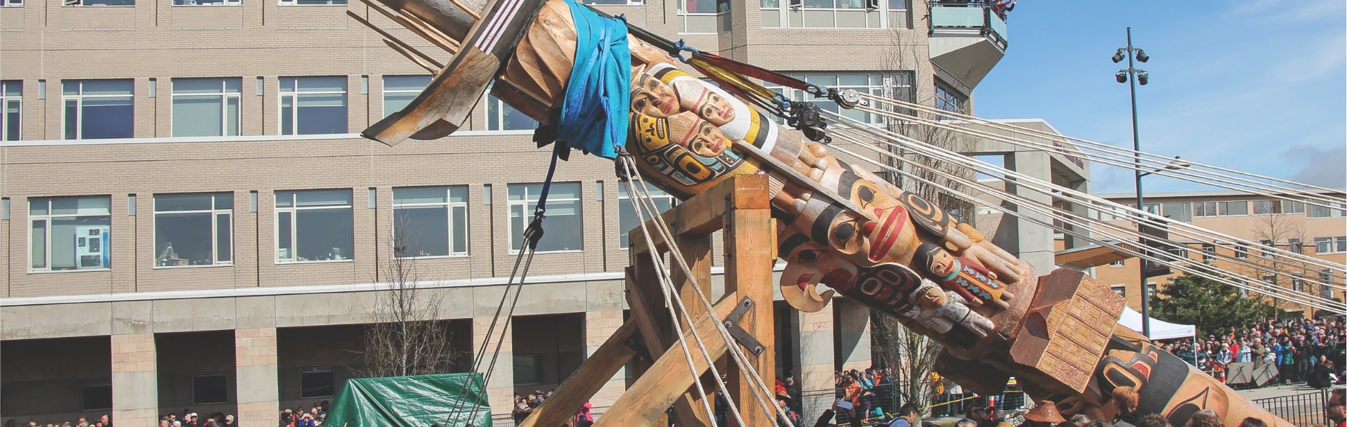 Photo of the raising of Reconciliation Pole. The pole is resting on supports with ropes attached to it.