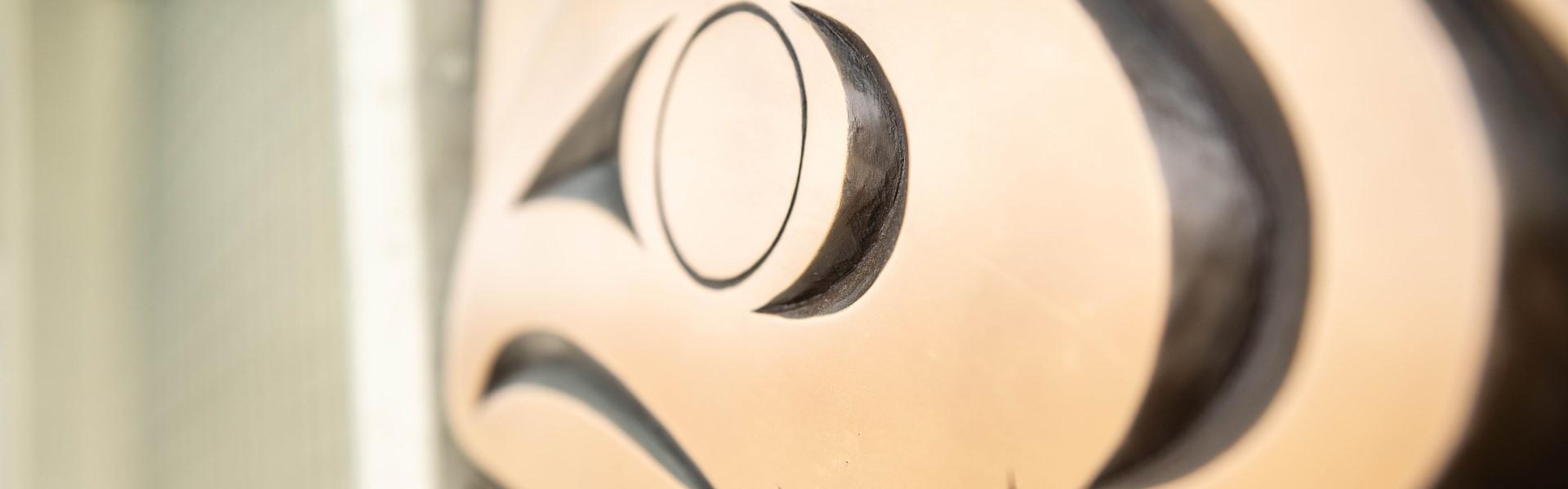 Photo of detail of ʔəlqsən — the hən̓q̓əmin̓əm̓ word for 'point of land' - an art installation at UBC Vancouver bus loop. The detail is of cast bronze carving of a salmon eye.